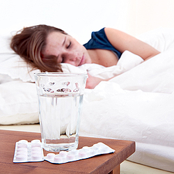 Glass of water and two strips of pills on a bedside table, with a sick woman sleeping in the background