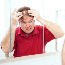 Middle aged man checking for thinning hair in the mirror.