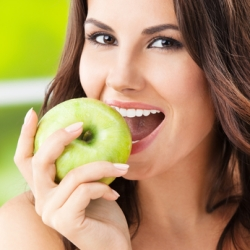 Portrait of young woman eating green apple, outdoors